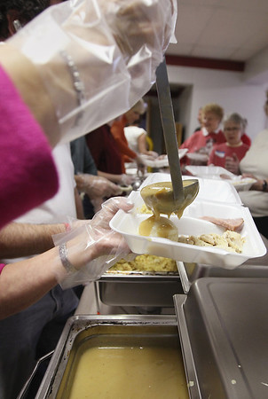Record-Eagle/Keith King<br /> Gravy is poured as volunteers serve food to attendees in Luther Hall at Trinity Lutheran Church Thursday, November 22, 2012 during the Community Meals Program's Thanksgiving Day meal.