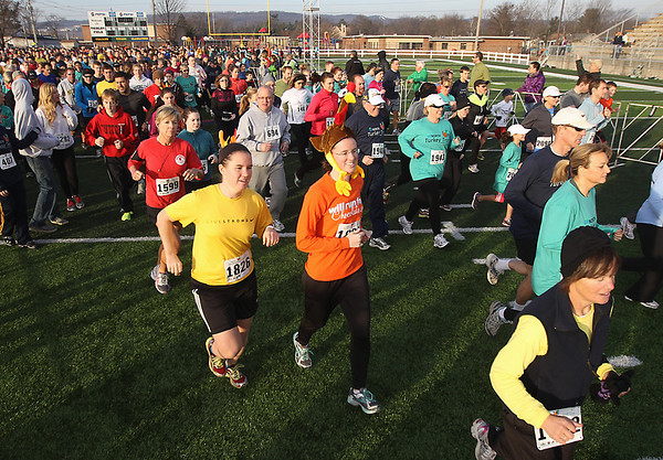 Record-Eagle/Keith King<br /> Maggie Troost, left, and Elizabeth Troost, right, both of Traverse City, are joined by others as they take off from the starting line Thursday, November 22, 2012 at Thirlby Field during the Traverse City Turkey Trot. More than 2,300 people were registered for the event.
