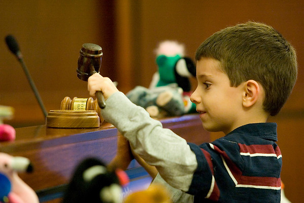 Record-Eagle/Jan-Michael Stump<br /> Geoffrey Pierick, 5, bangs the gavel to finalize his adoption by Jacqueline and Greg Baker before 13th Circuit Court Probate Judge David Stowe and Michigan Supreme Court Justice Alton Davis Tuesday.