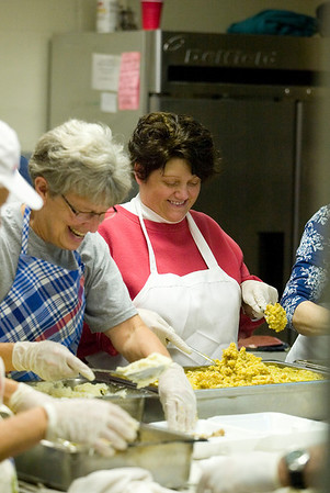 Record-Eagle/Jan-Michael Stump<br /> Eileen Wooer (cq), left, and Kerri James (cq) prepare Thanksgiving dinners with other volunteers at Trinity Lutheran Church Thursday morning. Volunteers prepared and delivered about 800 meals to area residents, then prepared another 350 meals to serve at the church. The volunteer effort is in its 22nd year, and is one of several in the Grand Traverse area bringing meals to those in need for the holiday.
