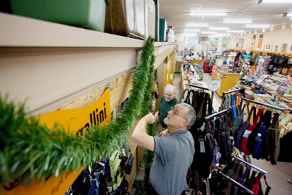 Record-Eagle/Keith King<br /> Kerry Glaesmer, foreground, vice president of Votruba Leather Goods Co., and employee Phil Stephenson, hang garland in the store Wednesday, November 24, 2010 as they prepare for the holiday shopping season.