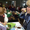 "Record-Eagle/Garret Leiva<br /> Nola Raven, 4, of Traverse City, plays with her tea set as her nana, Cathie Martin, of Traverse City, takes a sip of pretend tea while attending the Zonta Club of Traverse City Festival of Trees ""Dolly & Me Tea"" Sunday at Lobdell's Restaurant in the Hagerty Center. Moms, grandmothers and aunts brought their girls - and several dolls and teddy bears - to the three-course tea. Each table had an individual storybook theme. Girls also received a keepsake doll-sized ceramic teacup and saucer."