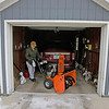 "Record-Eagle/Keith King<br /> Lee Hilbert, of Traverse City, backs his snowblower into his garage Friday after arriving home and pulling his vehicle into his garage. ""It's easier than driving over it and then trying to remove it,"" Lee said about why he positions the snowblower behind his vehicle."