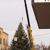 Record-Eagle/Jan-Michael Stump<br /> Traverse City's downtown Christmas tree is placed in Cass Street at Front Street. According to a scale in the crane, the tree weighed about 6,200 pounds before it was trimmed to fit the manhole it rests in.