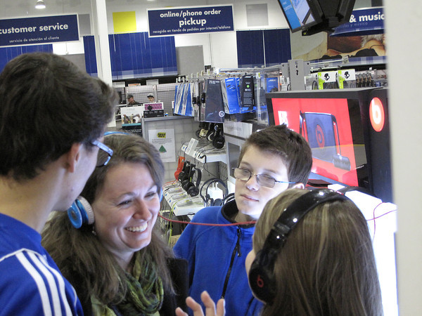 Record-Eagle/Glenn Puit<br /> Melinda Gall, center left, smiles while trying out a set of headphones with her children at Best Buy in Traverse City shortly after midnight Friday. Also pictured, from left to right, are Greg Long, Nick Long and Chloe Gall.