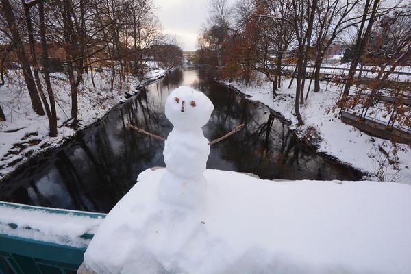 Record-Eagle/Dan Nielsen<br /> A miniature snowman adorns the rail of Union Street bridge over the Boardman River in downtown Traverse City.