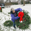 Record-Eagle/Keith King<br /> Carla Windover, of Long Lake Township, attaches a bow to a wreath as they are displayed Saturday, November 24, 2012 outside of the Traverse Bay United Methodist Church in Traverse City during the annual Wreaths for Haiti sale with proceeds going toward the Grand Traverse District United Methodist Volunteers in Mission (UMVIM) team's mission projects in Haiti. The team plans to fix wells, well sites and paths in rural southern Haiti. The sale is also scheduled to take place Saturday, December 1, 2012 from 9:30 a.m. until 3:30 p.m. The wreaths are put together in Leelanau County by volunteers with the greens of the wreaths coming from Nello Valentine's farm in Leelanau County.
