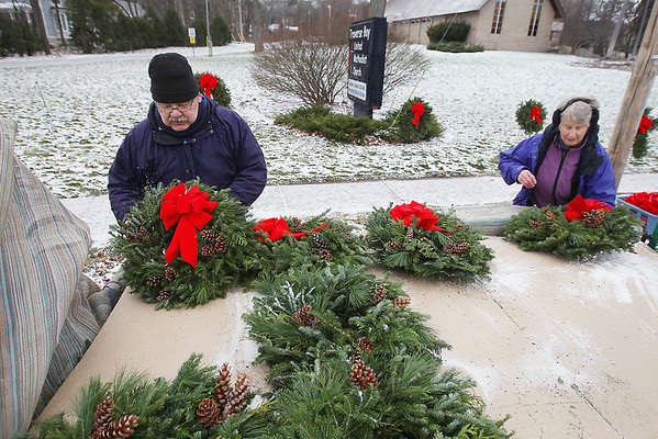 Record-Eagle/Keith King<br /> Michael and Carla Windover, of Long Lake Township, attach bows to wreaths prior to displaying them Saturday, November 24, 2012 outside of the Traverse Bay United Methodist Church in Traverse City during their annual wreath sale with proceeds going toward the Grand Traverse District United Methodist Volunteers in Mission (UMVIM) team's mission projects. The team plans to fix wells, well sites and paths in rural southern Haiti. The sale is also scheduled to take place Saturday, December 1, 2012 from 9:30 a.m. until 3:30 p.m. The wreaths are put together in Leelanau County by volunteers with the greens of the wreaths coming from Nello Valentine's farm in Leelanau County.