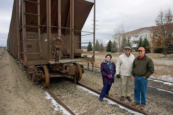 Record-Eagle/Keith King<br /> From left, Berneice Gonder, Dan Welburn and Randolph Lyon stand next to a railroad car stored on the tracks near their Lake Ridge condominium complex in Traverse City, shown behind them.