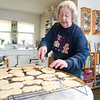 Record-Eagle/Jan-Michael Stump<br /> Maxcie Latimer places cookies on a rack to cool from the oven of her Traverse City home, where she'll bake about 120 dozen cookies for this year's Grace Episcopal Church cookie sale.