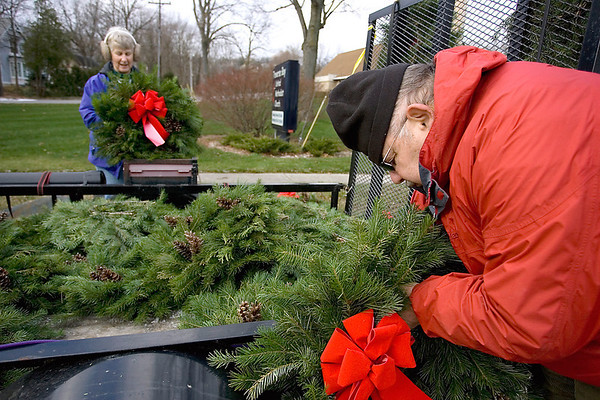 Record-Eagle/Keith King<br /> Michael Windover, right, of Traverse City, and his wife, Carla Windover, place bows on wreathes before displaying them for sale along Bay Street as part of Wreaths for Haiti. Money raised from the program will go toward repairing homes and installing a drip irrigation system in Mizak, Haiti. The wreath sale will continue Saturday, Dec. 4. The Windovers are members of the Grand Traverse District United Methodist Church Volunteer In Mission team.