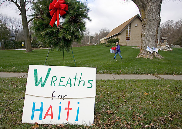 Record-Eagle/Keith King<br /> Carla Windover, of Traverse City, and a member of the Grand Traverse District United Methodist Church Volunteer In Mission team, carries a basket of bows that will be placed onto wreaths and sold along Bay Street for Wreaths for Haiti.
