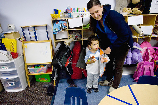Record-Eagle/Keith King<br /> Jennifer Bartlett, of Traverse City, helps her son, Makai Bartlett, 2, get his coat on at Angel Care Child Care prior to leaving for home.