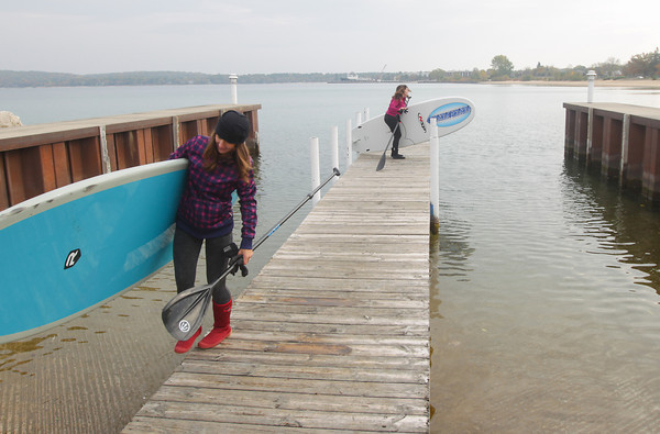 "Record-Eagle/Keith King<br /> Erica Whipple, left, and Sarah Hunt, of Lake Ann, carry their stand-up paddleboards Wednesday, October 30, 2013 after using them in West Grand Traverse Bay. ""It was really calm, super relaxing and the reflections are beautiful,"" Whipple said about the outing. ""It was very nice, the water was like glass,"" Hunt said after the two rode, and did yoga, on their paddleboards."