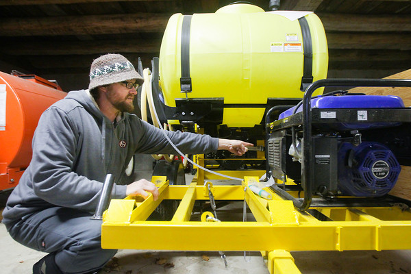 Record-Eagle/Keith King<br /> Jay Briggs, winemaker at Forty-Five North Vineyard and Winery in Suttons Bay Township, explains Wednesday, November 6, 2013 how a trailer (which includes a water reservoir, generator and sprayer) works once an ozone generator is placed on it.