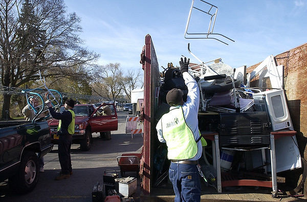 Record-Eagle/Garret Leiva<br /> Travis Fredette of Rifkin throws a metal frame into a Dumpster full of scrap metal at Daylight Savings Clean Up and Green Up community recycle Sunday in Parking Lot B in downtown Traverse City. The annual recycle event was sponsored by Michigan Green Consortium. Participants could bring in difficult-to-recycle items and products with salvageable components or materials to the free collection. A line of cars and trucks wrapped around the block as people brought in old television sets, refrigerators, building materials, small engines, auto batteries, computers, glass bottles, sinks, wire hangers, asphalt and a wide range of plastics and Styrofoam.