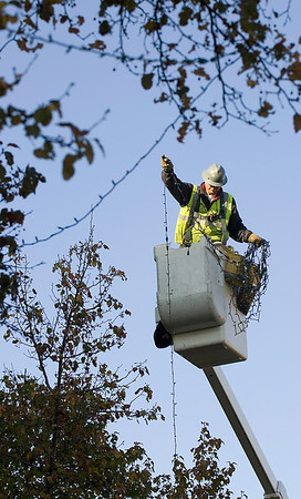 Record-Eagle/Keith King<br /> Jim Farrington, an employee with Traverse City Light & Power, hangs Christmas lights Tuesday, November 9, 2010 along Front Street in Downtown Traverse City.