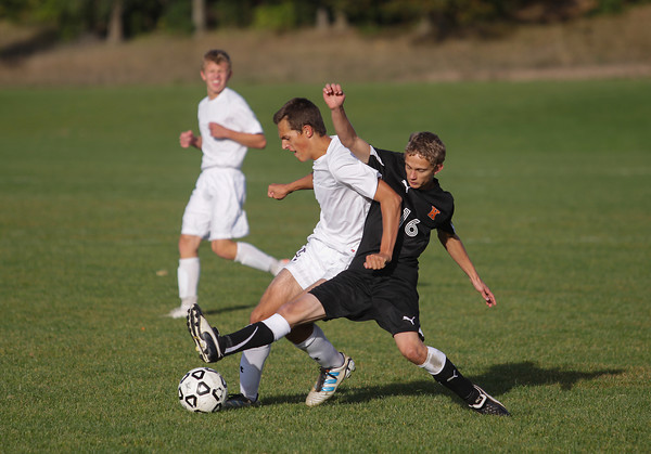 Record-Eagle/Keith King<br /> Traverse City Christian's Daniel Weber (12), left, and Kingsley's Justin Ginzel (16) battle for possession of the ball Monday, October 14, 2013 at the Keystone Soccer Complex.