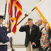 "Record-Eagle/Keith King<br /> U.S. Air Force veteran William Steffens,  of Petoskey, next to his wife, B.J. Steffens, and surrounded by family members as well as other attendees, salutes Thursday, October 17, 2013 at the U.S. Coast Guard Air Station Traverse City during a recognition ceremony for him.  In 1952, Steffens designed an emblem for the Air Rescue Service and entered it in a contest.  He never knew until February that it had become the service's official patch and is still used by the USAF Pararescue - an elite lifesaving  unit  that rescues downed and injured pilots in austere and dangerous places.  Steffens joined the military in 1943 at age 18. He served from  1943 to 1953 during World War II,  Korean War and Cold War as soldier, bombardier and radar technician. The patch combines an angel wrapping its wings  protectively around the globe and  the motto  ""That Others May Live.""  Steffens, who later taught school for many years, learned about the patch's existence while watching a  National Geographic show about helicopters.  More than 150 people, including Steffens six children, grandchildren, great-grandchildren and several local officials attended the ceremony."