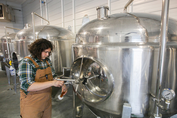 Record-Eagle/Keith King<br /> Michael Rizik, Beggars Brewery owner and head brewer, collects a beer sample Monday, October 14, 2013 to measure its sugar content.