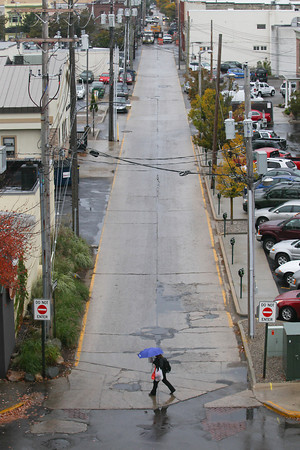 Record-Eagle/Keith King<br /> A pedestrian walks along Park Street in the rain Tuesday, October 15, 2013 in Traverse City.
