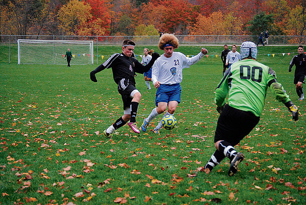 Record-Eagle/James Cook<br /> Leland forward Noah Fetterolf (4) advances the ball as Buckley's Bryce Guernsey (23) defends and Bears goalie Tyler Welch (00) approaches in Leland's 6-1 district championship win in Glen Lake.