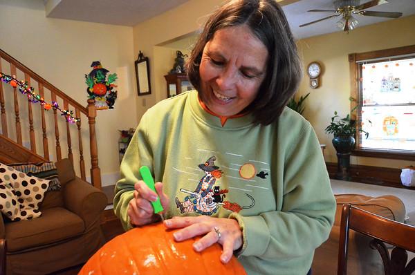 Record-Eagle/Allison Batdorff<br /> Nancy Rader carves a pumpkin in her Traverse City home.
