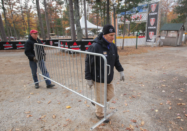 Record-Eagle/Keith King<br /> Volunteers Richard Wulf, left, of Traverse City, and Don Hrodey, of Lake Leelanau, carry a section of fencing Tuesday, October 29, 2013 at Timber Ridge Resort as preparations are made for the 24th annual Iceman Cometh Challenge mountain bike race events.