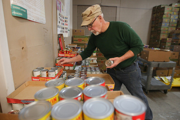 Record-Eagle/Keith King<br /> Volunteer Dennis Taylor sorts food Tuesday, October 8, 2013 at The Father Fred Foundation in Traverse City. The food is from The Father Fred Foundation Fall Food Drive.