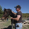 Record-Eagle/Keith King<br /> Larry Lelito, a United States Marine Corps veteran, stands with a horse Wednesday, October 2, 2013 at the Professional Equine Assisted Counseling and Education (PEACE) Ranch in Blair Township.