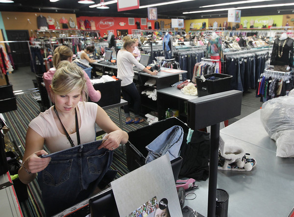 Record-Eagle/Keith King<br /> Courtney Cay, employee at Plato's Closet, makes a quote as she looks at clothes that were brought in to sell to the store Thursday, August 29, 2013 at Plato's Closet in Traverse City.