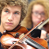 Record-Eagle/Nathan Payne<br /> Ellis Begley plays along under the direction of teacher Ellen Boyer at Traverse City Central High School. Symphony students at the school will have the chance to play at the Kennedy Center in Washington, D.C., in March.
