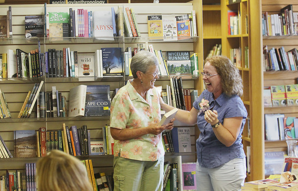 Record-Eagle/Keith King<br /> Sherry Day, left, is presented with a book written by former Kalkaska elementary school student of hers, Kitty Bucholtz, right, Saturday, September 7, 2013 at Horizon Books in Traverse City. Bucholtz, an author, dedicated a book the book to Day.