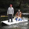 Record-Eagle photos/Glenn Puit <br /> Dick Swan, inventor of the Airborn inflatable boat, stands on the boat on the Boardman River on Monday as his friend, Brad Jones, paddles.