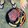 Record-Eagle/Jan-Michael Stump<br /> Jared Boynton of Traverse City grills flank steak, hot dogs and sausages during a Labor Day picnic with family and friends at Keith J. Charters Traverse City State Park.
