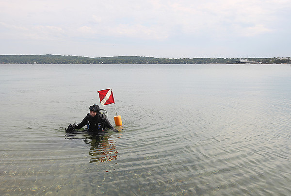 "Record-Eagle/Keith King<br /> Steven Johnson, of Traverse City, emerges from West Grand Traverse Bay at the Clinch Park boat launch Wednesday, September 5, 2012 after scuba diving before work. Johnson was looking at an old log pile as well as the underwater topography and contours of the bay. ""I had two large bass following me for about 30 minutes. I was kicking up the silt and they were seeing what they could pick up to eat,"" Johnson said. ""it's just enjoyable, you're in your own world down there. We're so fortunate to have this,"" Johnson said."