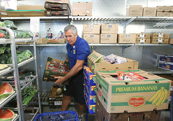 Record-Eagle/Keith King<br /> Bob Cullen, route manager with Food Rescue of Northwest Michigan, loads fruit and vegetables onto a cart Wednesday, August 29, 2012 at the Oleson's food store located at Oleson's Plaza East in Traverse City.