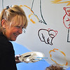 Record-Eagle/Vanessa McCray<br /> <br /> Kathy Wollam paints a mural Thursday at Central Day Care Center in Traverse City as part of the Day of Caring.