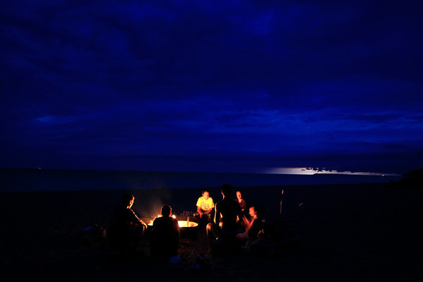 Record-Eagle/Jan-Michael Stump<br /> From left, Nate Schlehuber, Zach Lane, Eric Freeman, JohnPaul Morris, Julie Freeman and Alaina Stevens sit around a campfire at Empire Beach while lightning flashes on the horizon on Monday evening.