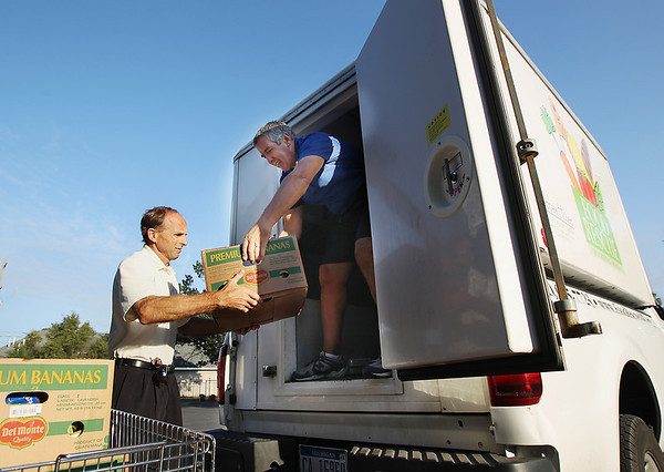 Record-Eagle/Keith King<br /> Bob Cullen, right, route manager with Food Rescue of Northwest Michigan, hands food to Norman Bamberg, operations director with the Father Fred Foundation, Wednesday, August 29, 2012 at the Father Fred Foundation.