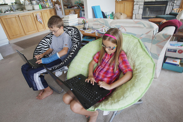 Record-Eagle/Keith King<br /> Micah Thoreson, left, 12, and Jenaya Thoreson, 9, utilize computers Friday, September 6, 2013 at their home.