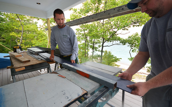 Record-Eagle/Dan Nielsen<br /> Andy Desmond, left, helps trim a piece of siding on a house being built north of Frankfort just steps from a Lake Michigan beach.