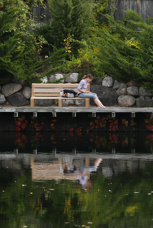 Record-Eagle/Keith King<br /> Jessica Cichowski, of Traverse City, reads during her lunch break Thursday, October 3, 2013 along the Boardman River in Traverse City.