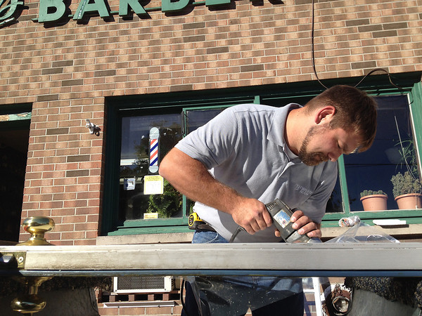 Record-Eagle/Matt Troutman<br /> Ian Marshall, a residential glazier with Twin Bay Glass, on Wednesday cuts open a door frame to accommodate a new window for Jere's Barber Shop, 110 S. Oak St., after an overnight break-in.