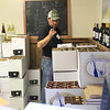 Record-Eagle/Jan-Michael Stump<br /> Justin Leshinsky unpacks cases of 2011 and 2010 wine at Bowers Harbor Vineyards Monday.