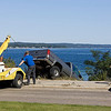Record-Eagle/Keith King<br /> Emergency personnel stand nearby as a pickup truck is pulled from an embankment between Grandview Parkway and West Grand Traverse Bay on Wednesday.