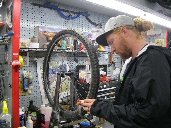 Record-Eagle/Carol Thompson <br /> Brick Wheels Service Technician Grayson Wiggins trues a wheel at the store on Sept. 5.