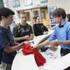 Record-Eagle/Keith King<br /> Shale Perkette, far left, standing next to Daniel Kyser, buys a Traverse City Patriot Game t-shirt from Sammy Schriber, with the Traverse City West High School Student Senate, Thursday, September 12, 2013 at Traverse City West High School.