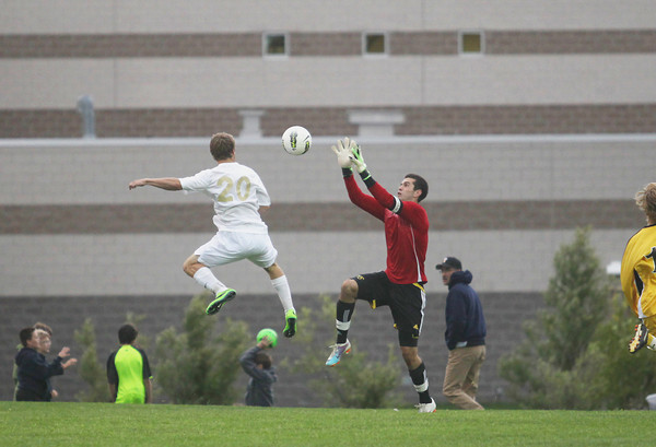 Record-Eagle/Keith King<br /> Traverse City Central goalkeeper Carl Gardner jumps for the ball against Traverse City West's Christien Geiger (20) Thursday, September 12, 2013 at Traverse City West High School.