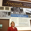"""Peg Sicilliano, archivist at the History Center, stands in front of the new exhibit entitled, """"Legends of the Grand Traverse Region: community out of Diversity."""""""